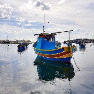 Blue-boat-docked-in-Marsaxlokk-s-Bay,-Malta