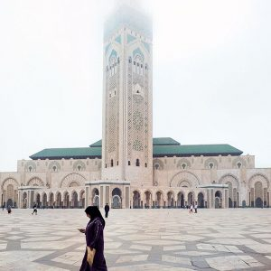 Moroccan-woman-in-front-of-Hassan-II-Mosque,-Casablanca